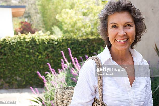 Woman outside home with large purse smiling