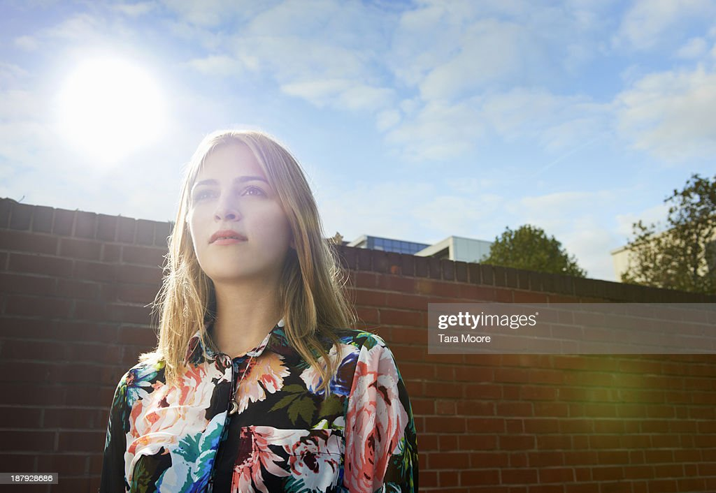 woman outside looking up with sunlight