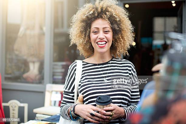 Woman outside shop holding reuseable coffee cup
