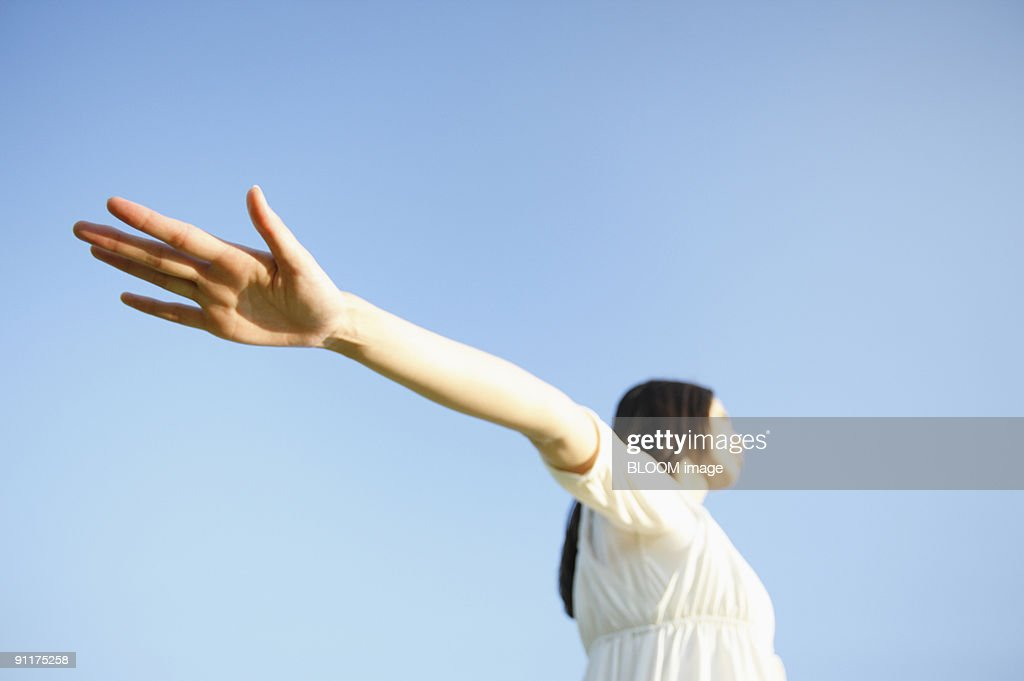 Woman outstretching arms, against sky