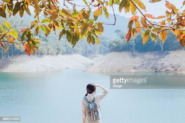Woman overlooking by the lake with eyes shielded