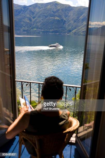 Woman overlooking rural lake from balcony, Lugano, Ticino, Switzerland