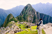 Woman sitting on a ledge and overlooking the Inca ruins of the city of Machu Picchu seen in the background.