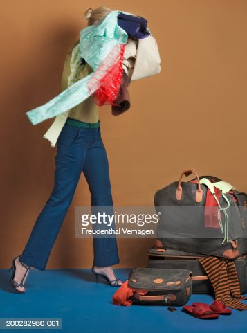 woman packing clothes in luggage side view stock foto getty images. Black Bedroom Furniture Sets. Home Design Ideas