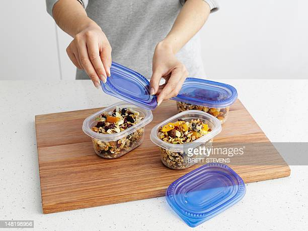 Woman packing granola in tupperware