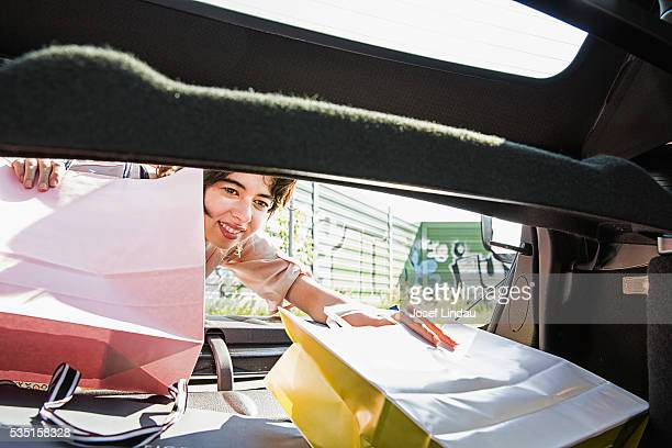 Woman packing shopping bags into her car