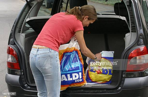 Woman packs shopping bags of Lidl and Aldi into her car