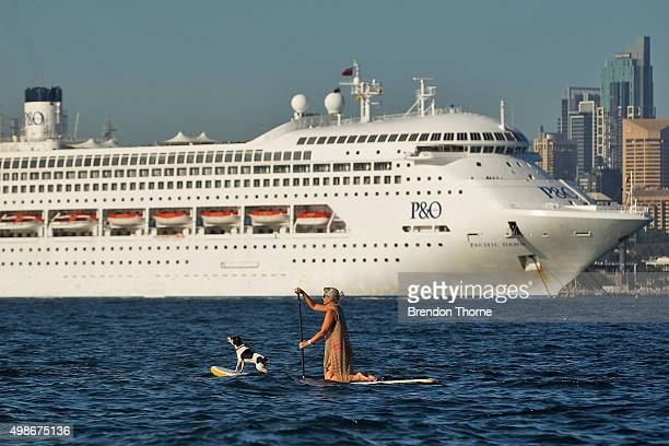 A woman paddle boards with her dog as PO's Pacific Dawn is moored in Sydney Harbour on November 25 2015 in Sydney Australia The maritime event is the...