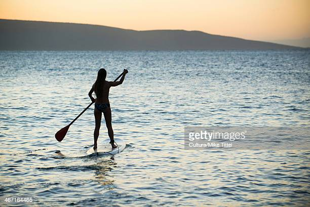 Woman paddleboarding on ocean
