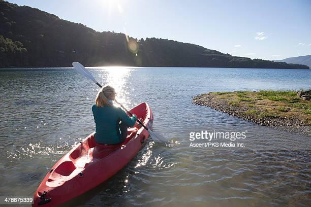 Woman paddles kayak along lakeshore, sunrise