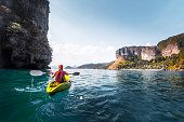 Woman paddles kayak in the calm sea among the tropical islands