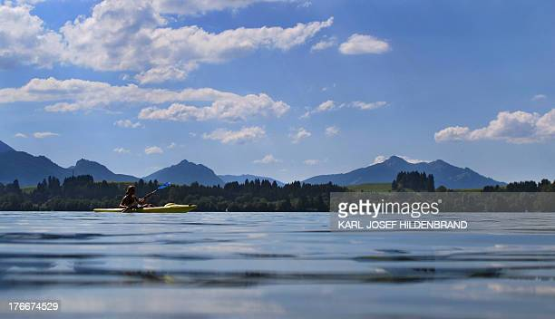 A woman paddles over the Forggensee lake near Fuessen southern Germany on August 16 2013 AFP PHOTO / DPA / KARLJOSEF HILDENBRAND / GERMANY OUT