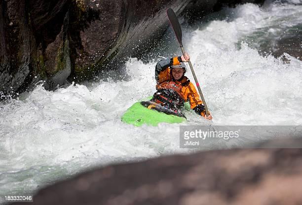 Remo una mujer de blanco de agua en Kayak por el río de montaña