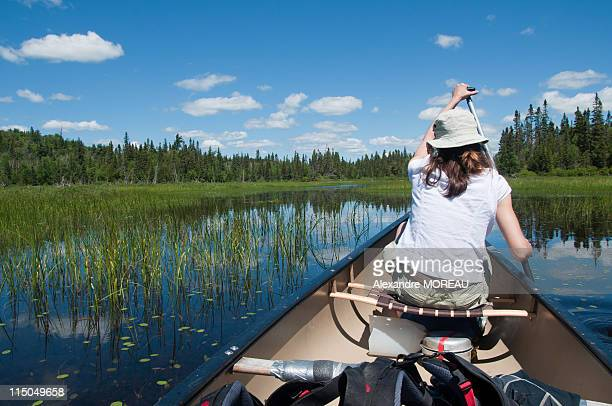 Woman paddling for wandering canoe trip in Canada