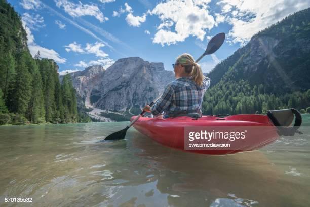 Woman paddling red canoe on beautiful lake