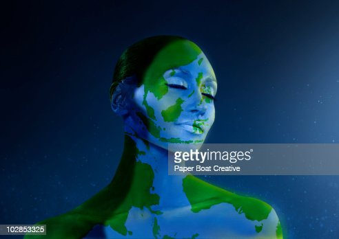woman painted as planet earth, facing the sun : Stock Photo