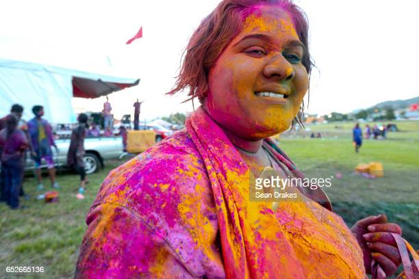 A woman painted with colorful abeer powder poses during Holi which celebrates the arrival of the season of Spring as part of the annual Phagwah...