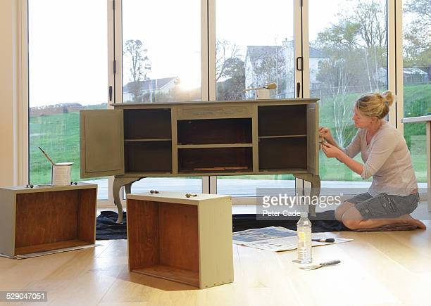 woman painting a cupboard in house