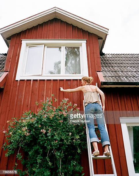 A woman painting a house.