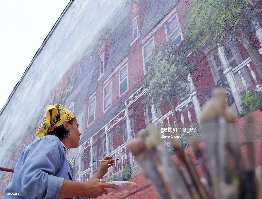 A woman painting a picture of a house : Stock Photo