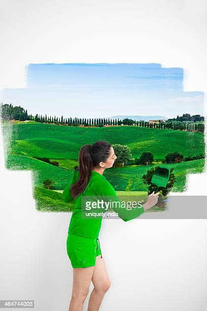 Woman painting a scenery on a wall