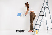beautiful attractive woman painting wall with paint roller in blue color
