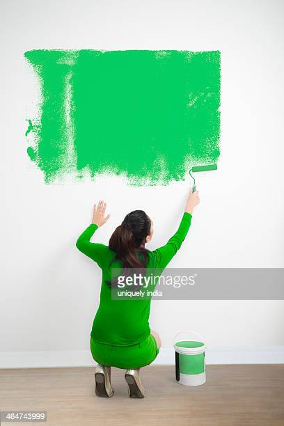 Woman painting a wall with a green color