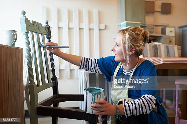 Woman painting chair in workshop.