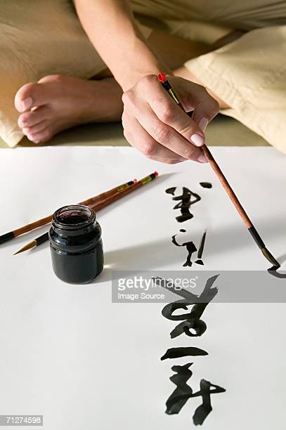 Woman painting chinese symbols