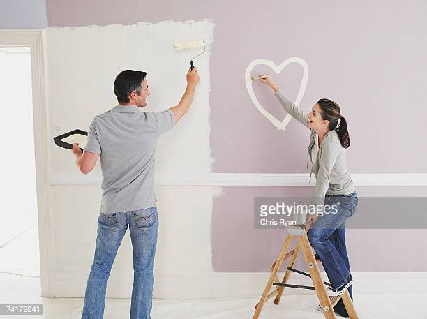 Woman painting heart on wall in room with man