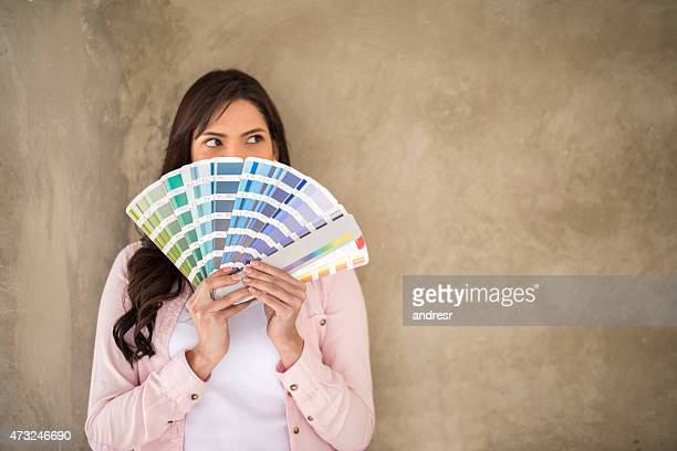 Woman painting her house and thinking about the color