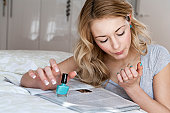 Woman painting her nails in bedroom