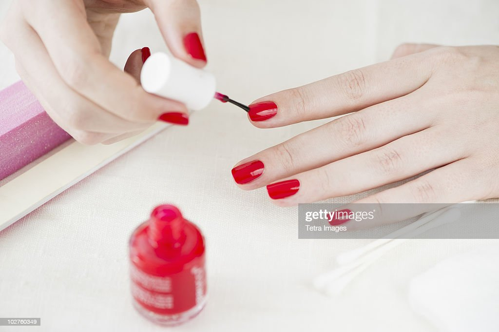 Woman painting her nails with red nail polish