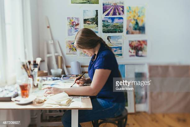 Woman painting in studio.