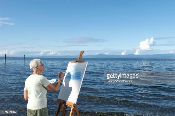 Woman painting near ocean