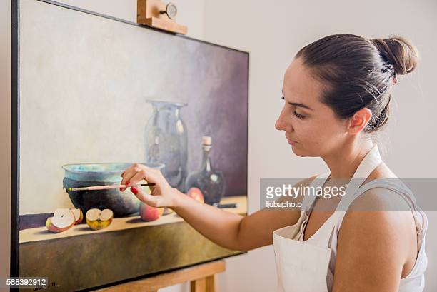 woman painting on canvas for fun at home