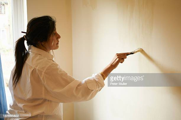 Woman painting room with paintbrush