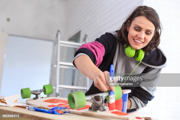Woman painting skateboard