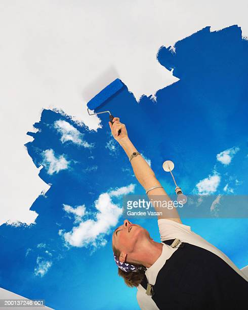Woman painting sky across ceiling, low angle view (Digital Composite)