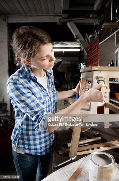 Woman painting stool in workshop