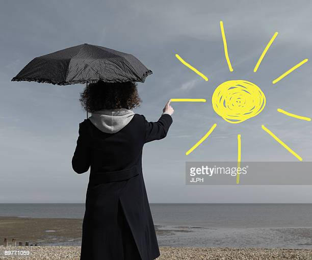 Woman painting sun onto grey sky