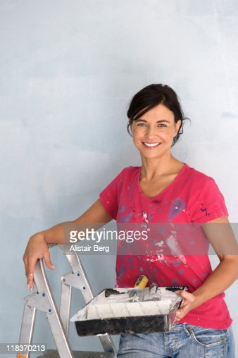 Woman painting wall : Stockfoto