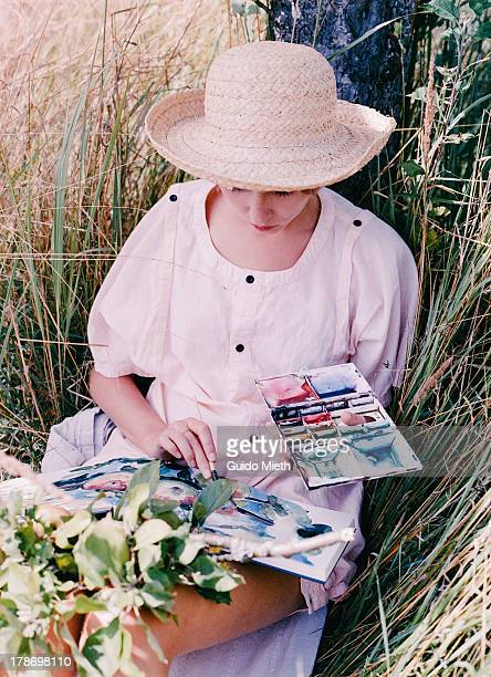 Woman painting watercolour outdoor.
