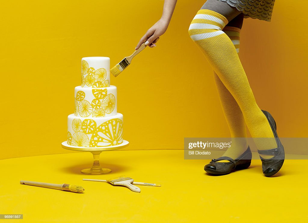 Woman painting wedding cake : Stock Photo