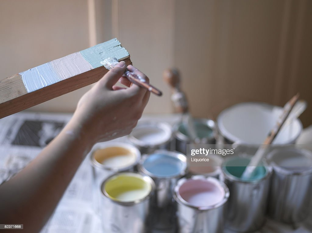 woman painting wooden batton