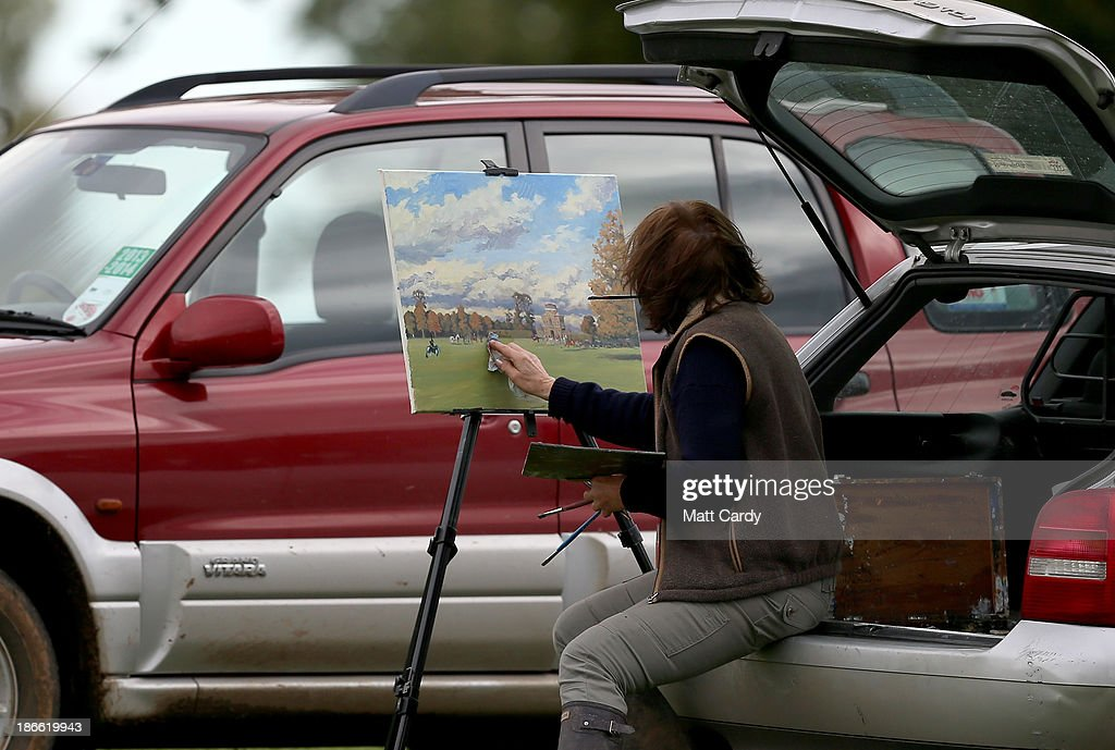 A woman paints as riders from the Duke of Beaufort's Hunt arrive with the hounds for their opening meet of the season at Worcester Lodge on November 2, 2013 near Badminton in Gloucestershire, England. Traditionally the hunting season starts at the beginning of November and although a ban on fox hunting with dogs has been in force since February 2005, many supporters of fox hunting are continuing to call for a repeal of the ban, saying the current law is hard to interpret and enforce.