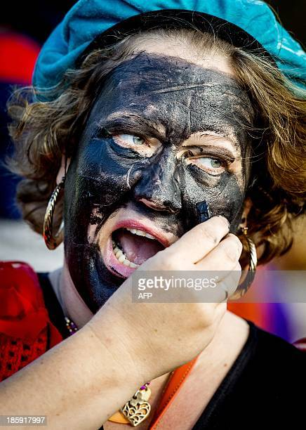 A woman paints her face black as she dresses up as Zwarte Piet during a demonstration in favor of the character SaintNicholas' helper at the...