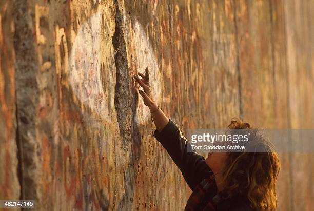 A woman paints onto the Berlin Wall on the morning of its fall on the 10th November 1989