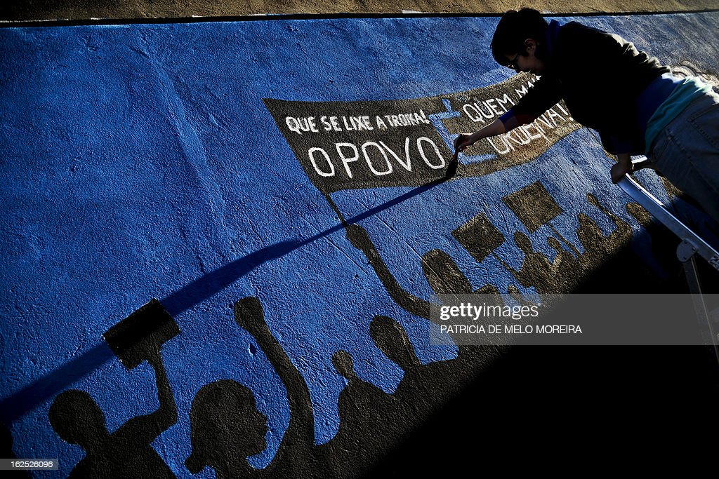 A woman paints part of a mural reading 'Damn theTroika! The power lies in the People' in Lisbon on February 24, 2013. The mural by the 'Damn the Troika' movement calls for participation in a protest against government's austerity measures in Lisbon on March 2. AFP PHOTO / PATRICIA DE MELO MOREIRA