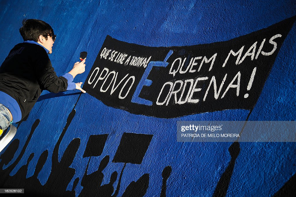 A woman paints part of a mural reading 'Damn theTroika! The power lies in the People' in Lisbon on February 24, 2013. The mural by the 'Damn the Troika' movement calls for participation in a protest against government's austerity measures in Lisbon on March 2.
